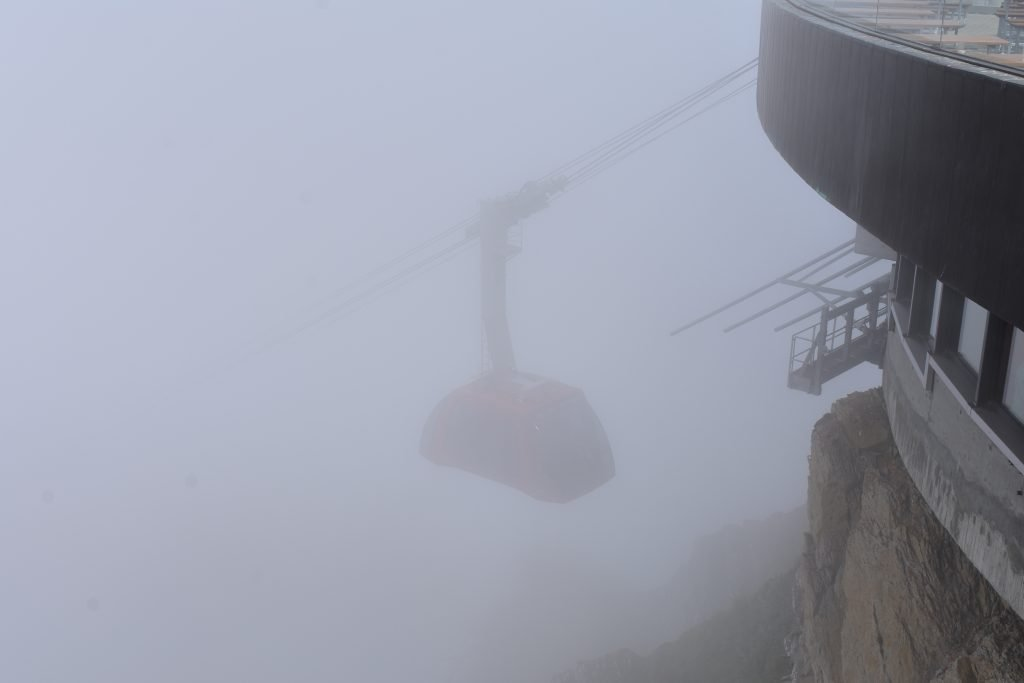 a gondola disappears into the gray cloud bank of the mountainside
