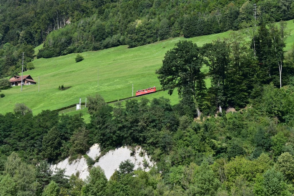 red cogwheel train climbs a mountainside as part of the mount pilatus golden tour